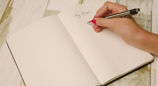 Girl writing her plans on a notebook