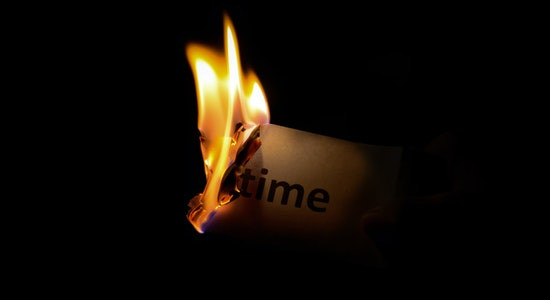Burning paper with the word time written on it
